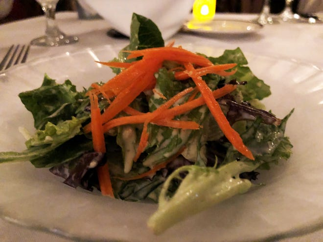 The complimentary house salad tossed in a homemade black peppercorn and garlic vinaigrette from Bistro Soleil, Marco Island.