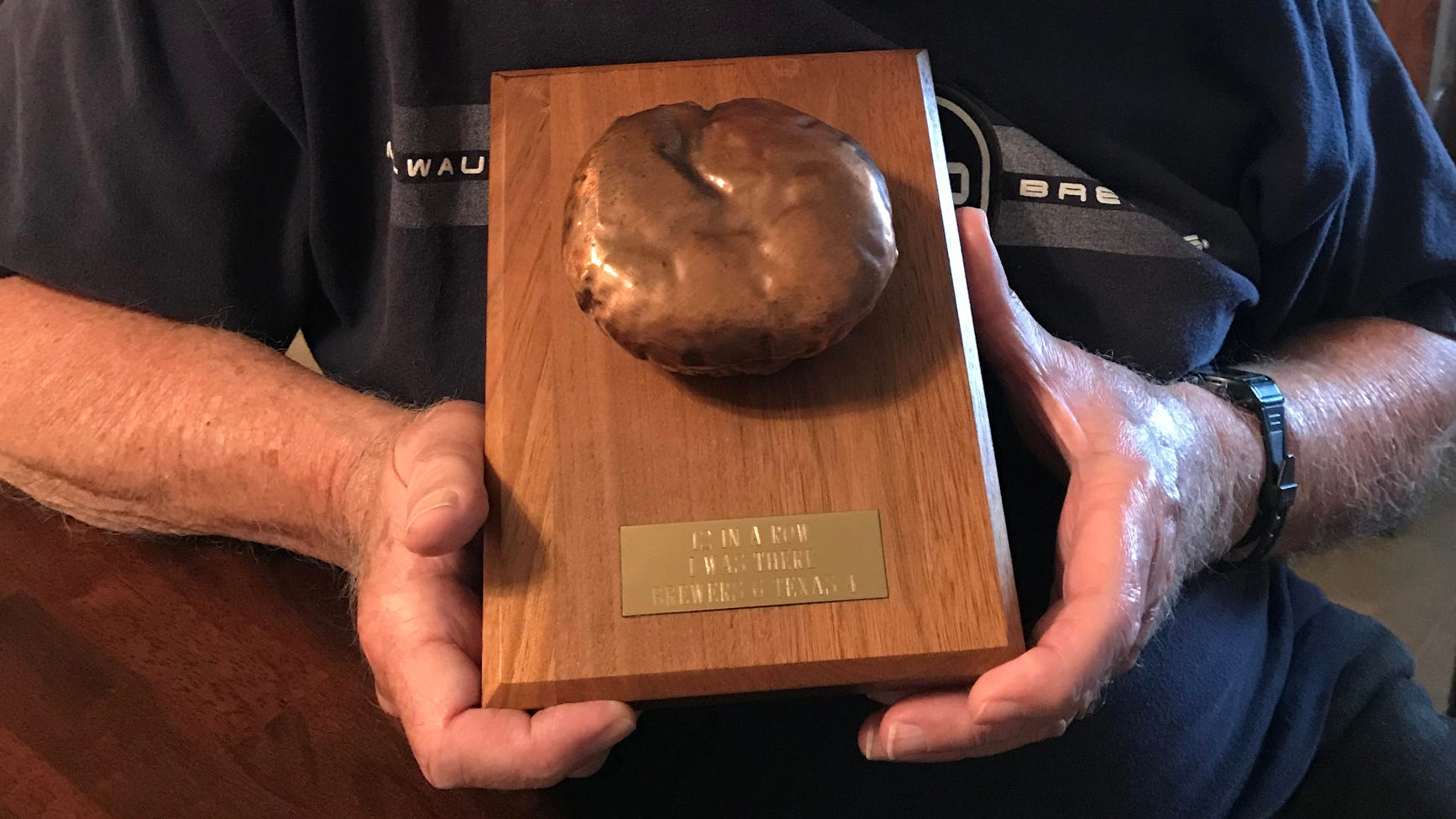 Mark Leaver Sr. holds the bronzed 1987 free George Webb's hamburger his son gave him for Father's Day 31 years ago.