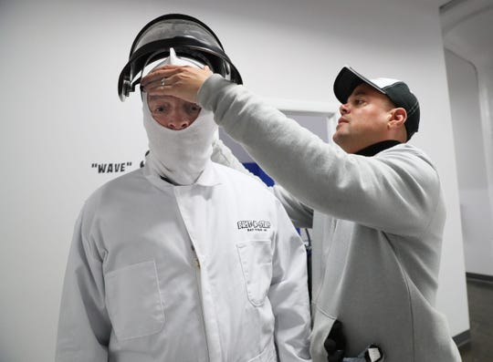 Eugene Trotter (left), owner of Bust-N-Stuff, helps Jim Stingl don a protective face mask.