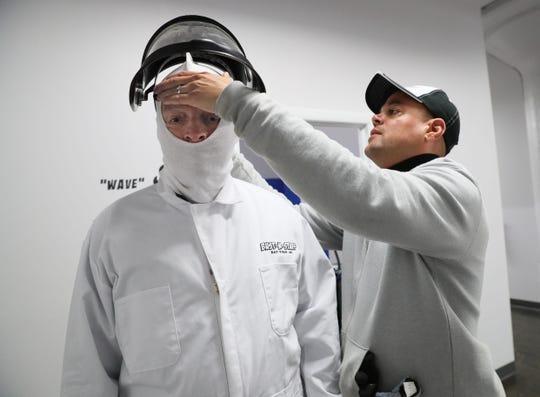 Eugene Trotter (left), owner of Bust-N-Stuff, helps Jim Stingl don a protective face mask.
