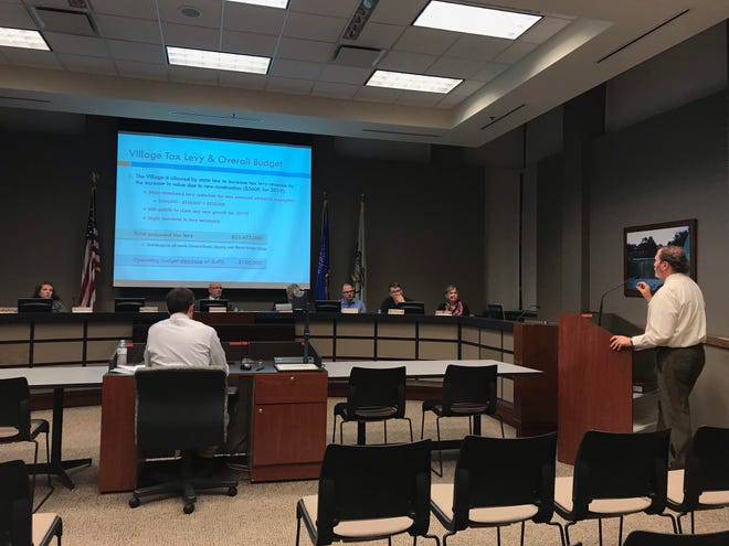 Village manager Mark Fitzgerald (right) explains the proposed budget to the village board.