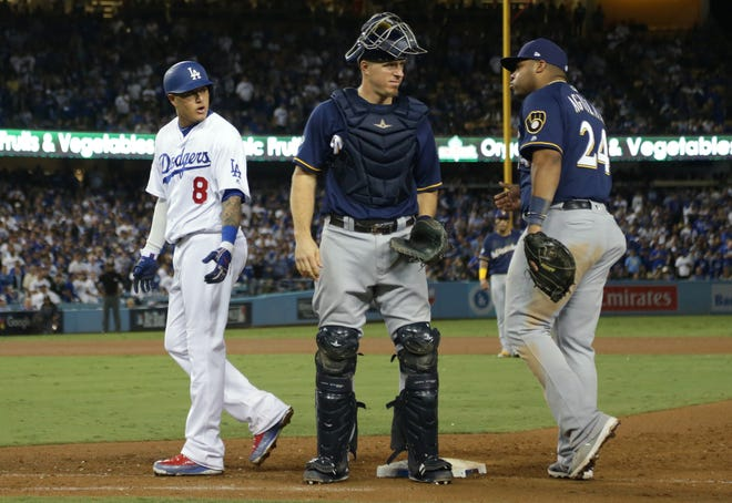 Brewers catcher Erik Kratz stands between first baseman Jesus Aguilar and the Dodgers' Manny Machado after an incident at first base in the 10th inning of Game 4 on Tuesday.