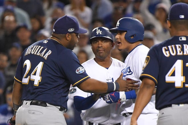 Manny Machado of the Dodgers (right) and Jesus Aguilar (24) have a tense exchange during the 10th inning of Game 4 of the NLCS on Oct. 16.