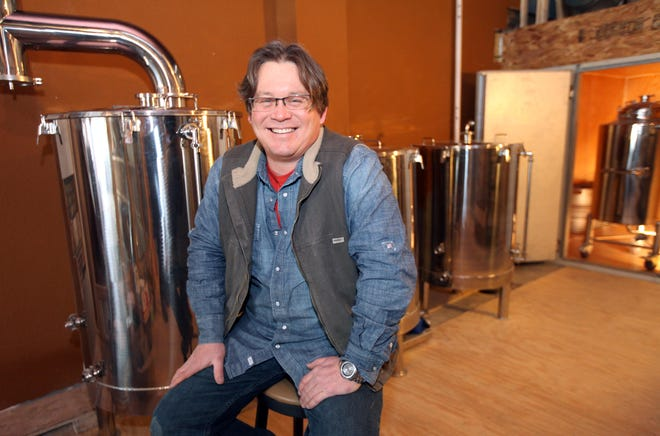 Matt McCulloch sits near brewing kettles at D14 as he was preparing the space to open in January 2014.