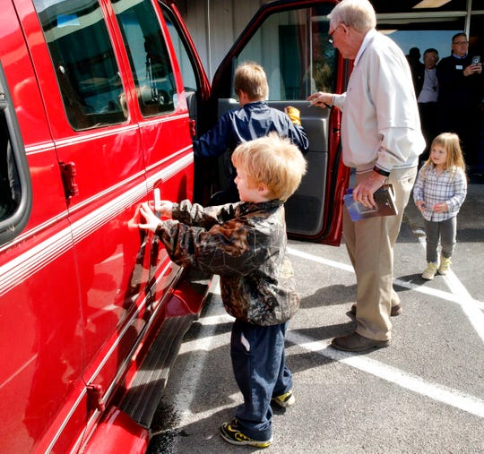 Greenhouse Ministries co-founder Cliff Sharp helps James, Luke and Sarah Caldwell explore the handicap-accessible van their parents were given on Wednesday, Oct. 17, 2018.