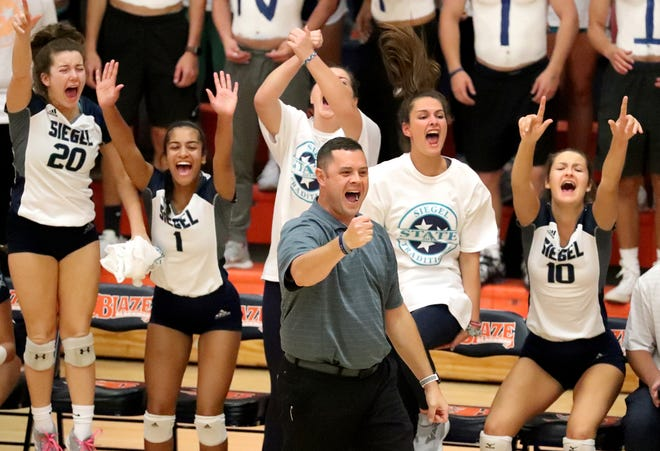 Siegel volleyball coach Shawn Robinson and his bench react to a point during Wednesday's state volleyball tournament action.