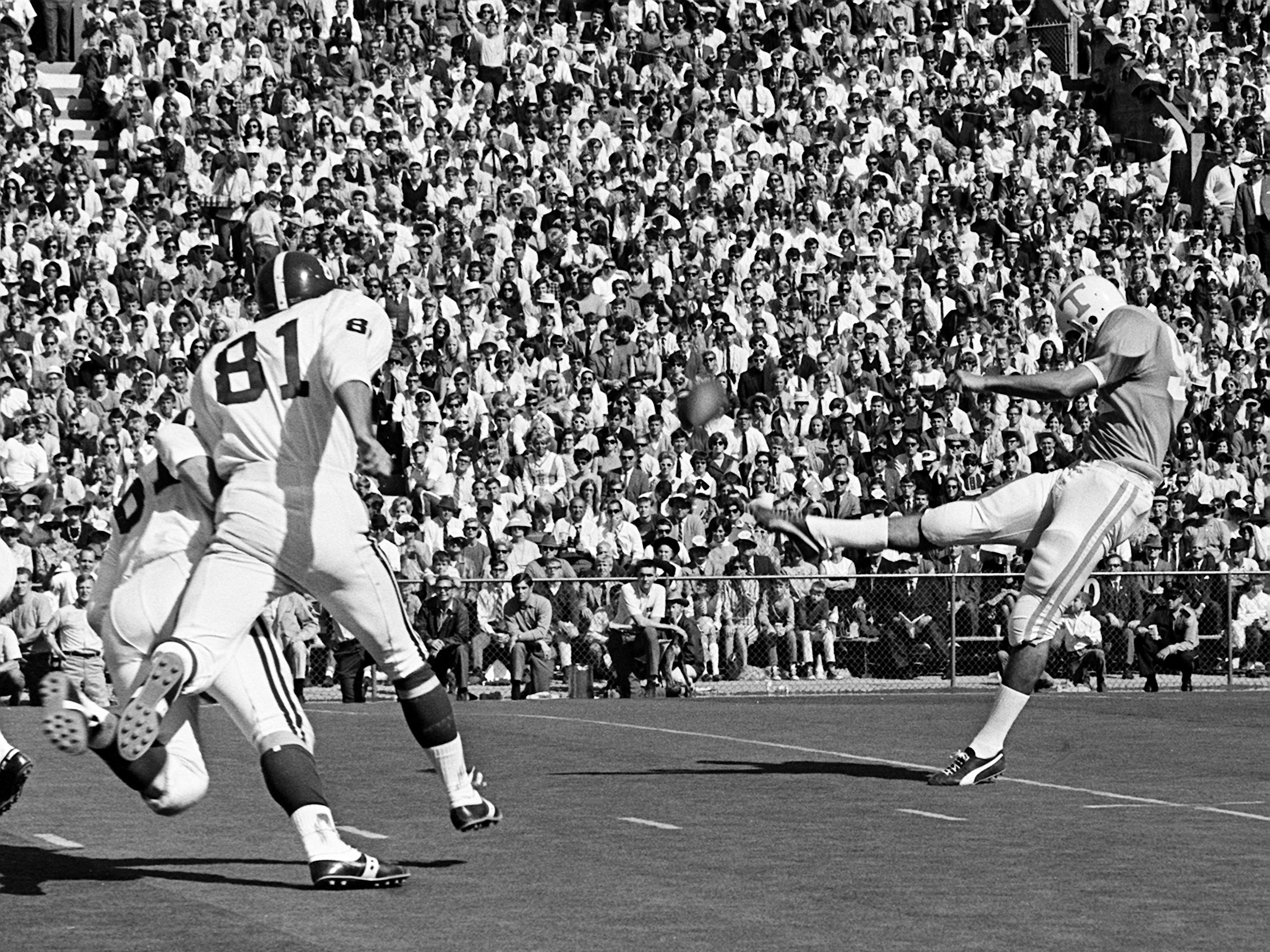 Tennessee junior punter Herman Weaver, right, gets his punt off against Alabama. Weaver, the nation's leading punter with 44-yard average, had a 36.9-yard average in the game as Tennessee survived a missed two-point conversion, an onside kick and a missed field goal in the final minute and 12 seconds to win 10-9 over Alabama at Neyland Stadium Oct. 19, 1968.