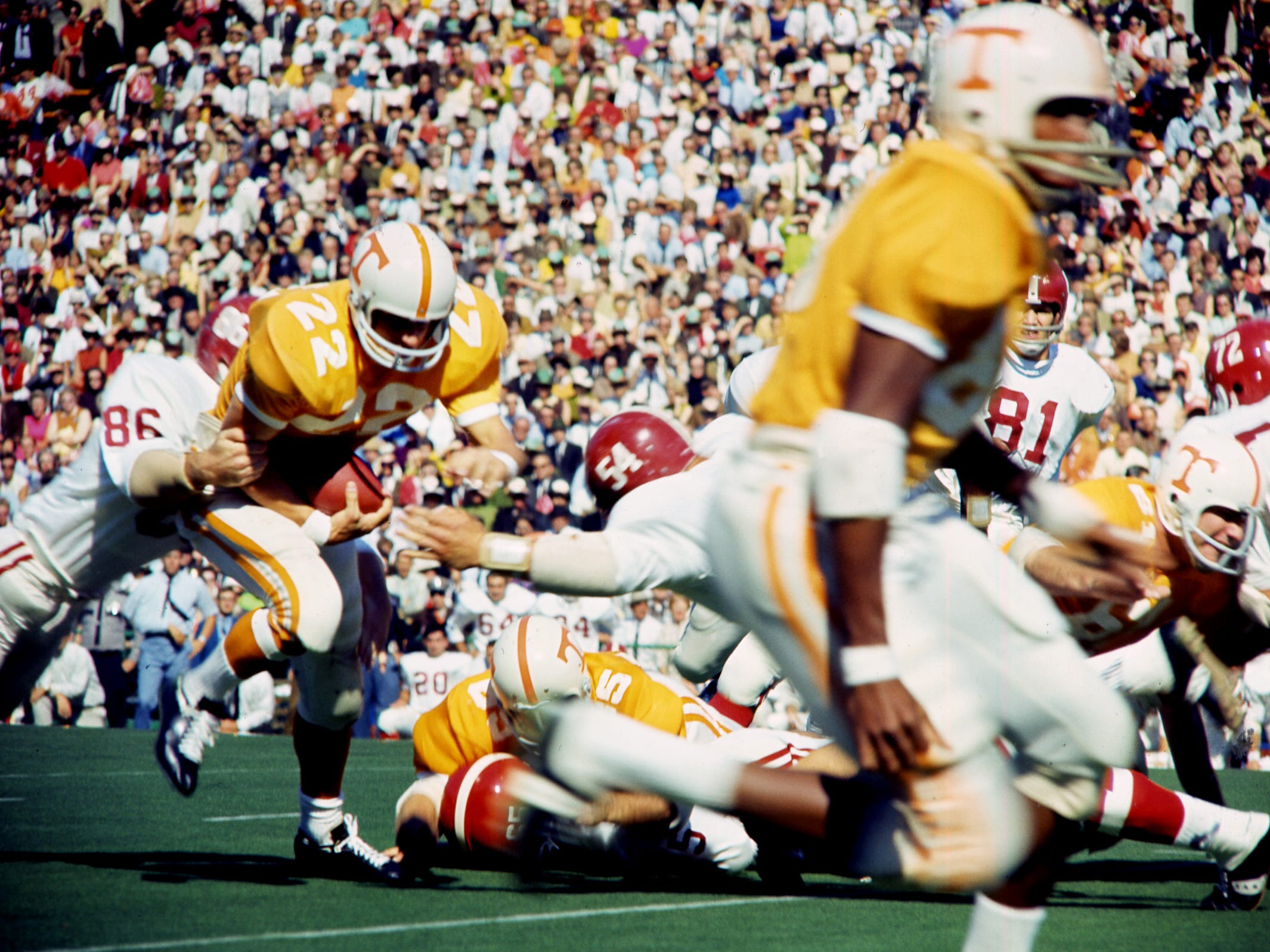 Tennessee senior back Richmond Flowers (22) is caught from behind by one Alabama defender as another, linebacker Mike Hall (54), comes in head on before 63,392 fans at Neyland Stadium Oct. 19, 1968.