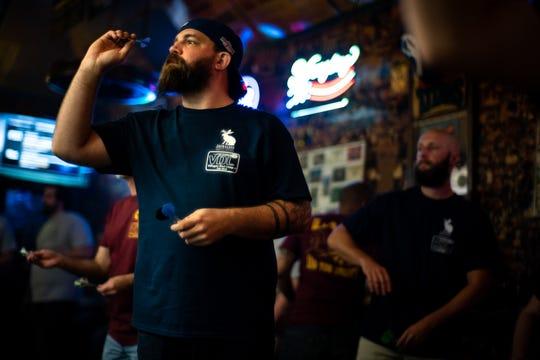 Dagan Crews aims before throwing during a dart league event at The Villager Tavern in Nashville, Tenn., Tuesday, Oct. 16, 2018.