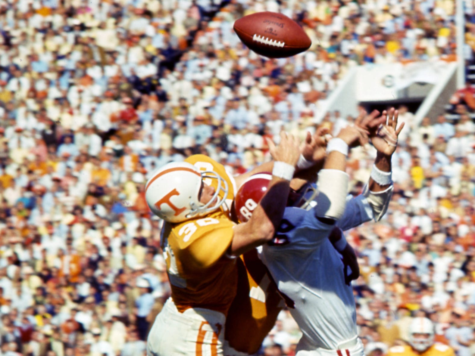 Tennessee defensive backs Bill Young (14) and Jim Weatherford (30) smacks Alabama receiver Conrad Fowler (89) to break up a pass near the goal line before 63,392 fans at Neyland Stadium Oct. 19, 1968.