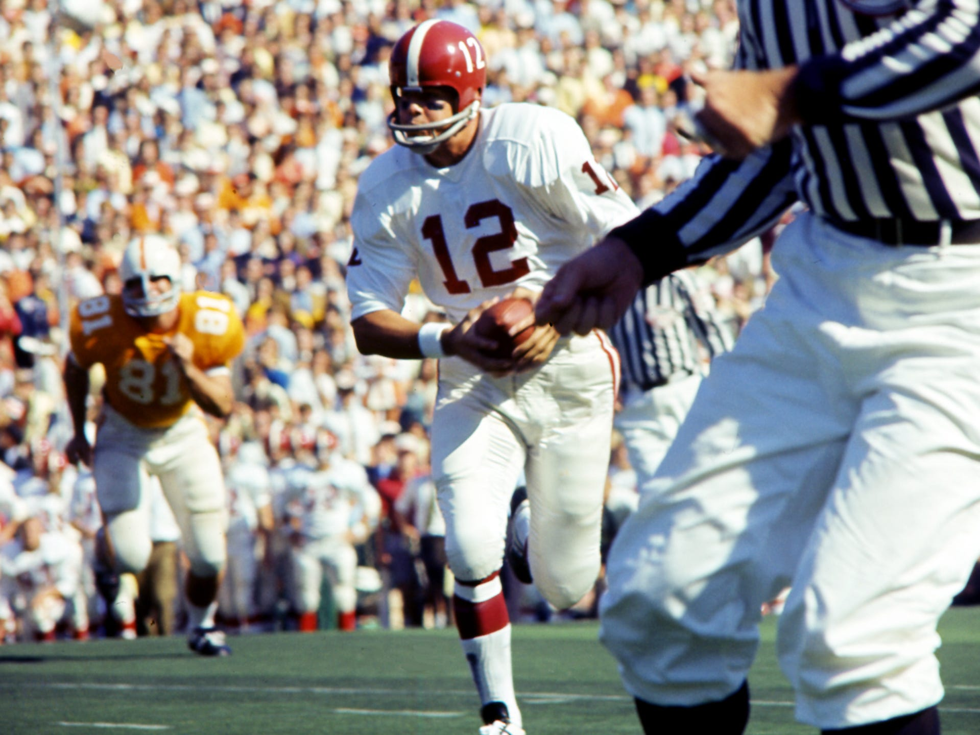 Alabama quarterback Scott Hunter (12) takes off running against Tennessee. Tennessee survived a missed two-point conversion, an onside kick and a missed field goal in the final minute and 12 seconds to win 10-9 over Alabama before 63,392 fans at Neyland Stadium on Oct. 19, 1968.