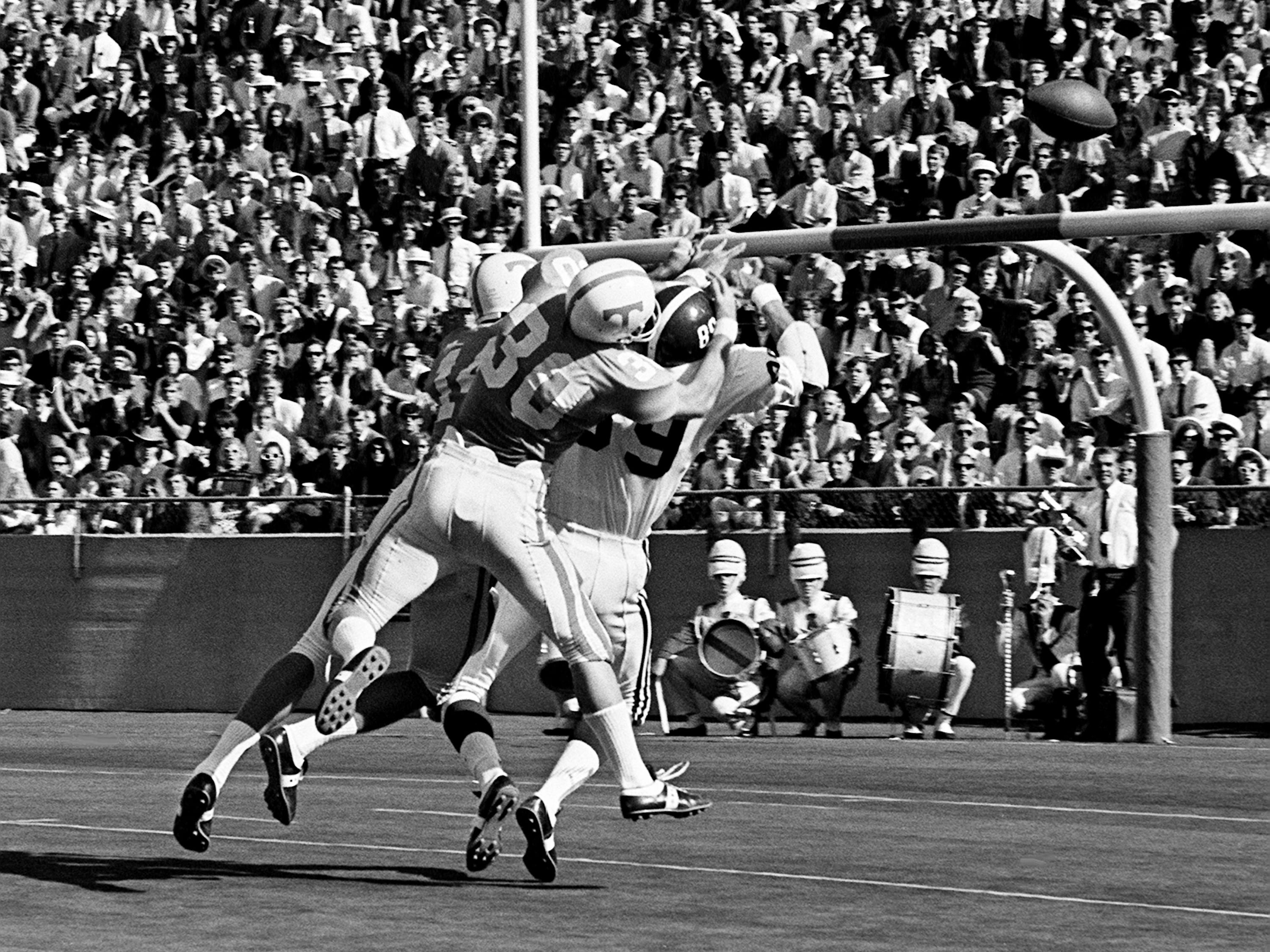 Tennessee defensive backs Bill Young (14) and Jim Weatherford (30) smacks Alabama receiver Conrad Fowler (89) to break up a pass near the goal line at Neyland Stadium Oct. 19, 1968.