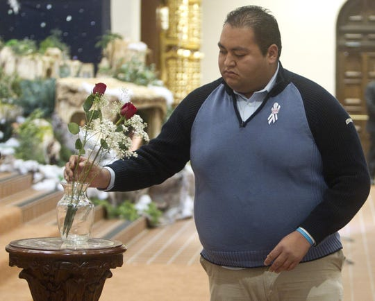 Gabrielle Giffords' former intern Daniel Hernandez places a rose in a vase honoring John Roll during an interfaith service held at St. Augustine Cathedral remembering the shooting on Jan. 8, 2011.