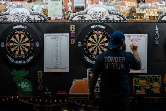 Dagan Crews writes his score during a dart league event at The Villager Tavern in Nashville, Tenn., Tuesday, Oct. 16, 2018.
