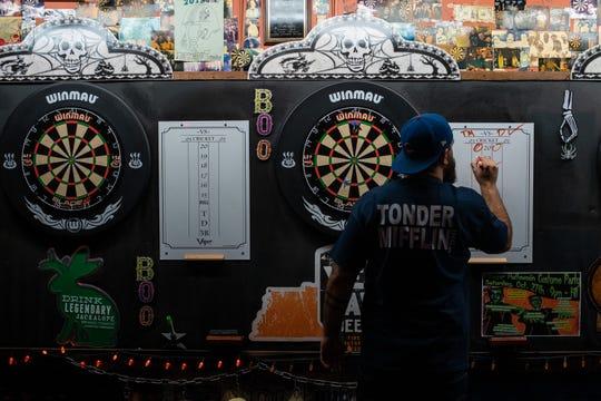 Dagan Crews writes his score during a dart league event at The Villager Tavern in Nashville, Tenn., Tuesday, Oct. 16, 2018.