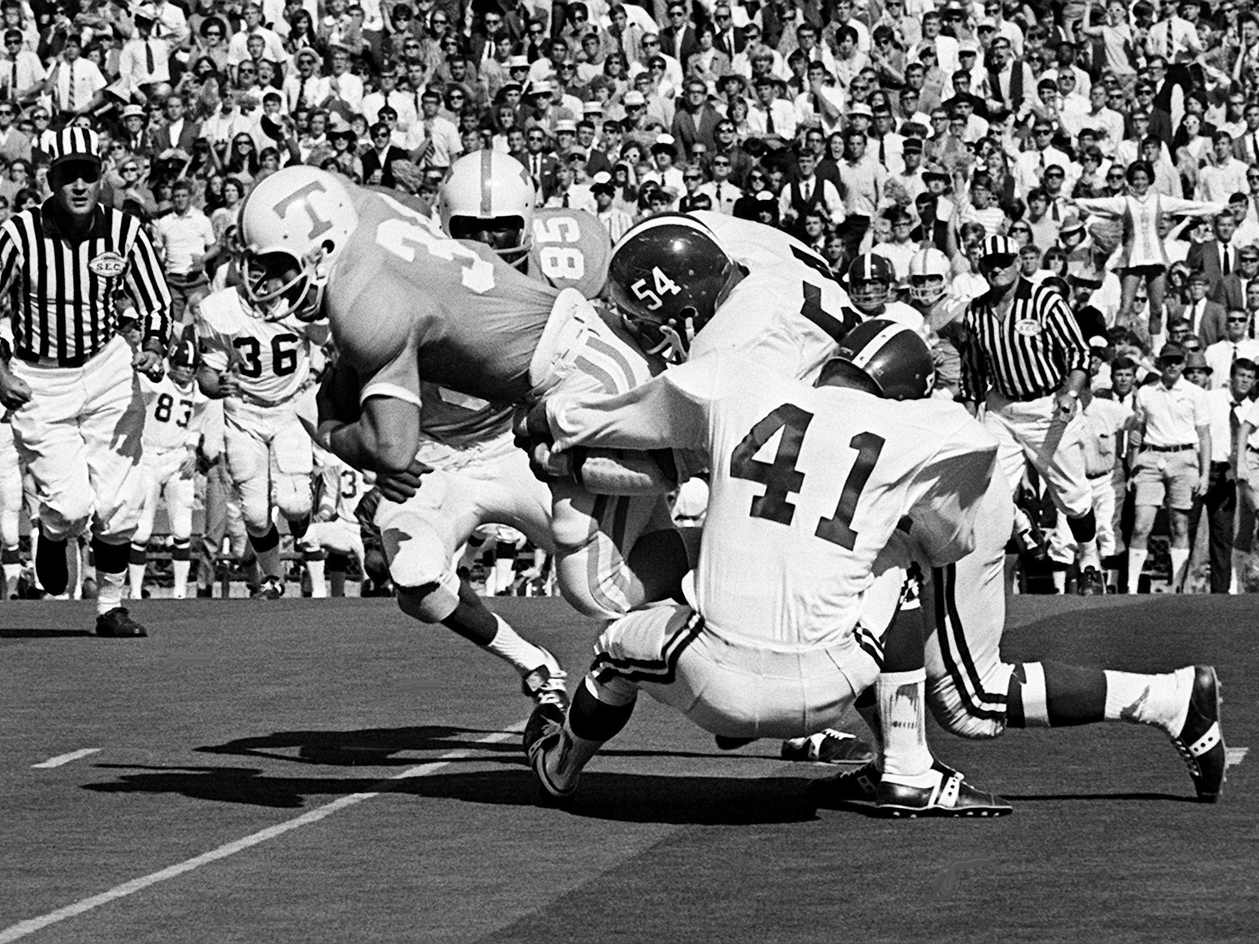 Tennessee senior fullback Richard Pickens (34) gets grabbed from behind by Alabama linebacker Mike Hall (54) and another defender at Neyland Stadium Oct. 19, 1968.