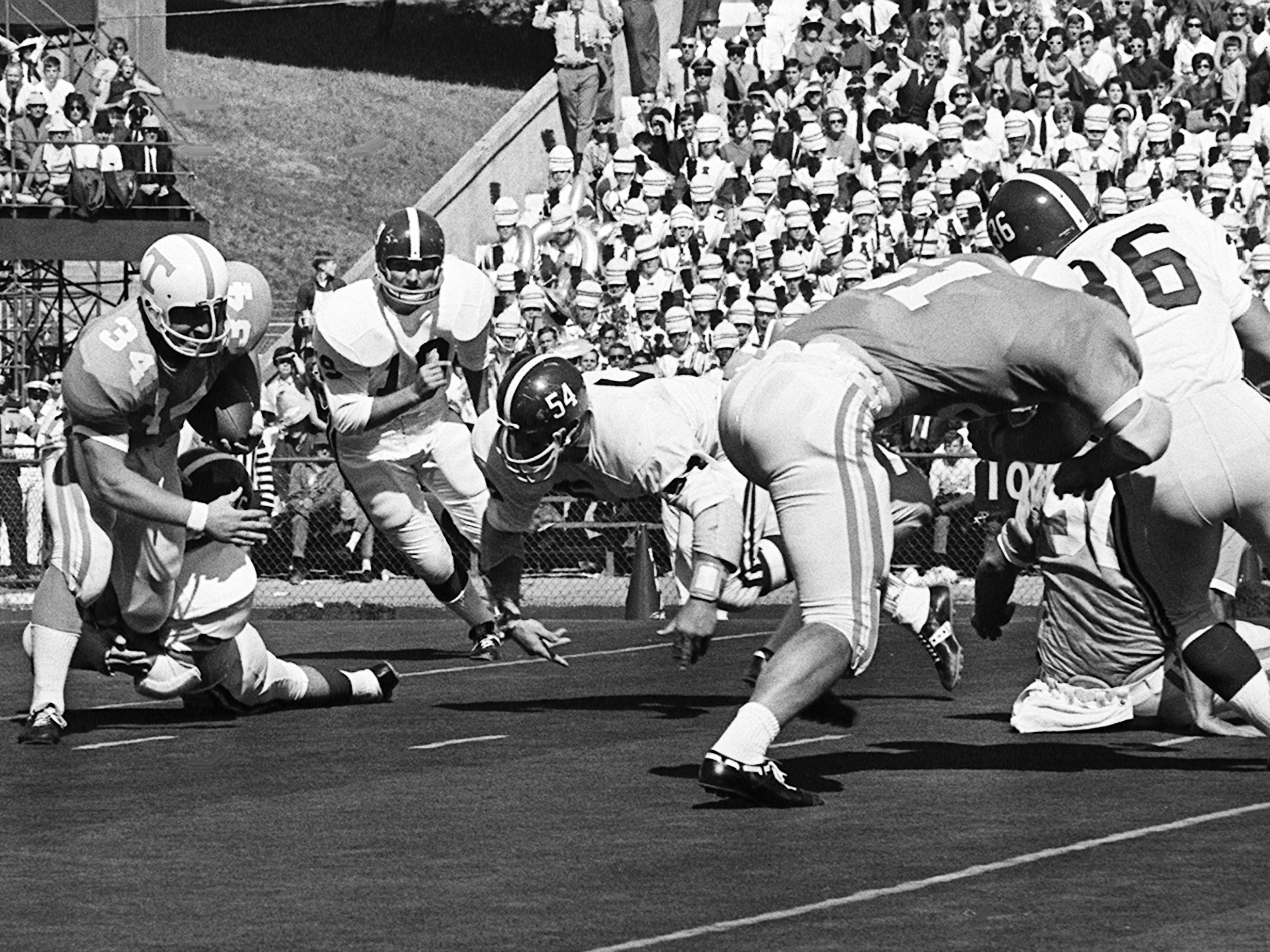 Tennessee senior fullback Richard Pickens (34) attempts to break the hold of one defender as other Alabama players close in on him at Neyland Stadium Oct. 19, 1968.