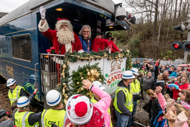 Ricky Skaggs hands out packages at a stop on the CSX Santa Train trail through Appalachia in 2017. The train delivers toys, food and winter clothes to families on a 110-mile trek from Kentucky to Tennessee.