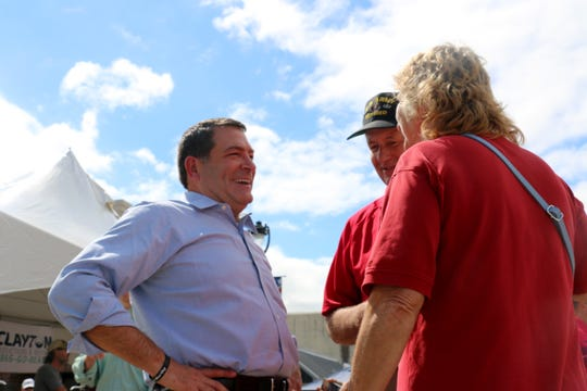 Mark Green leans back into a laugh as he talks with residents in Henderson, Tenn., on Sept. 28
