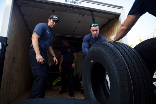 The rescue team loads three spare tuck tires along with their luggage and gear, as the Greater Naples Fire Rescue team heads North to the heavily impacted communities of Springfield and Callaway in Panama Beach City, on Wednesday Oct. 17, 2018, to relief their comrades who have been working at the location for over a week.
