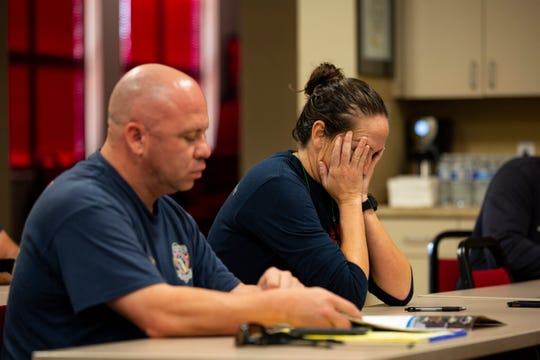 Erin Gill, an engineer at the Greater Naples Fire Rescue, rubs her face before the early morning briefing about their travels to Panama City Beach, Fla. on Oct. 17, 2018.