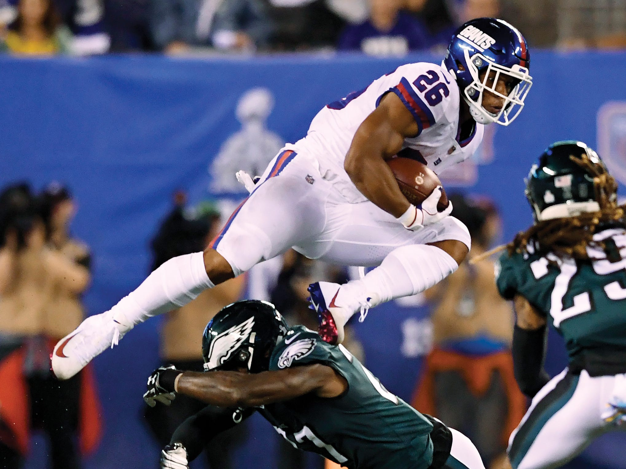 New York Giants running back Saquon Barkley (26) jumps over an Eagles defender in the first half. The New York Giants face the Philadelphia Eagles on Thursday, Oct. 11, 2018, in East Rutherford. (Danielle Parhizkaran/@danielleparhiz)