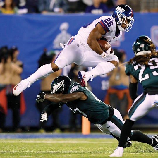 New York Giants running back Saquon Barkley (26) jumps over an Eagles defender in the first half. The New York Giants face the Philadelphia Eagles on Thursday, Oct. 11, 2018, in East Rutherford. (Danielle Parhizkaran/@danielleparhiz)