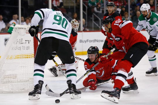 New Jersey Devils defenseman Sami Vatanen (45) knocks the puck away from Dallas Stars center Jason Spezza (90) in front of Devils center Travis Zajac (19) in the first period of an NHL hockey game Tuesday, Oct. 16, 2018, in Newark.