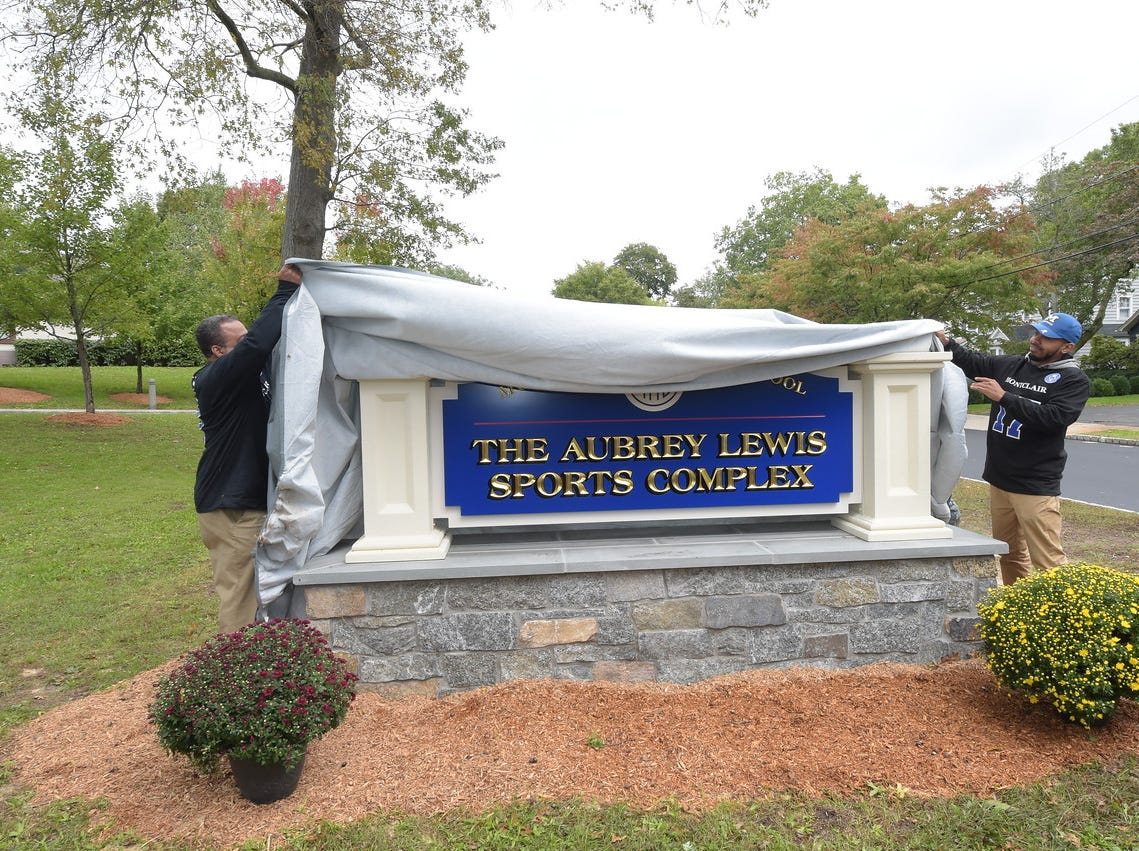 Family members unveil the sign for Montclair High School's Aubrey Lewis Sports Complex. October 13, 2018.