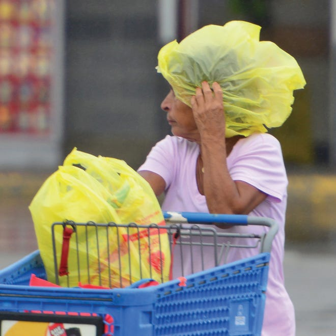 Una mujer utiliza bolsas del mandado para cubrirse de la lluvia.