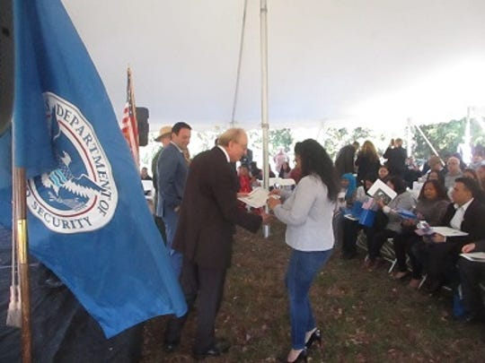 Esmeralda Ramirez receives her certificate of naturalization from John Thompson, District Director of the United States Citizenship and Immigration Services.