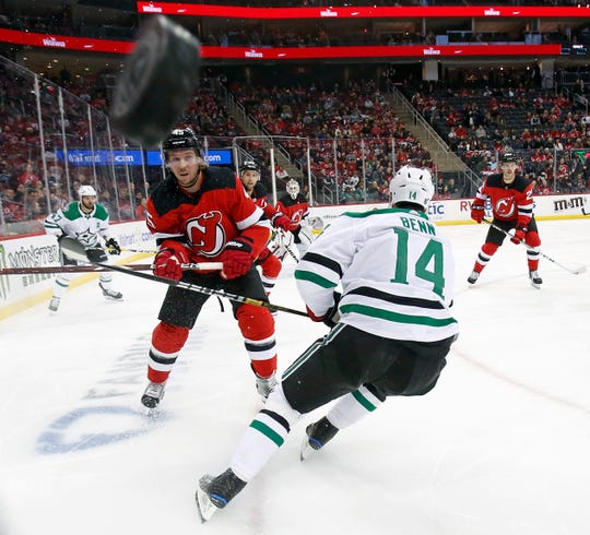 New Jersey Devils defenseman Sami Vatanen (45) clears the puck past Dallas Stars left wing Jamie Benn (14) in the first period of an NHL hockey game Tuesday, Oct. 16, 2018, in Newark.
