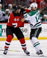 New Jersey Devils' Miles Wood (44) fights with Dallas Stars' Jamie Benn in the third period of an NHL hockey game Tuesday, Oct. 16, 2018, in Newark, NJ. The Devils won 3-0.