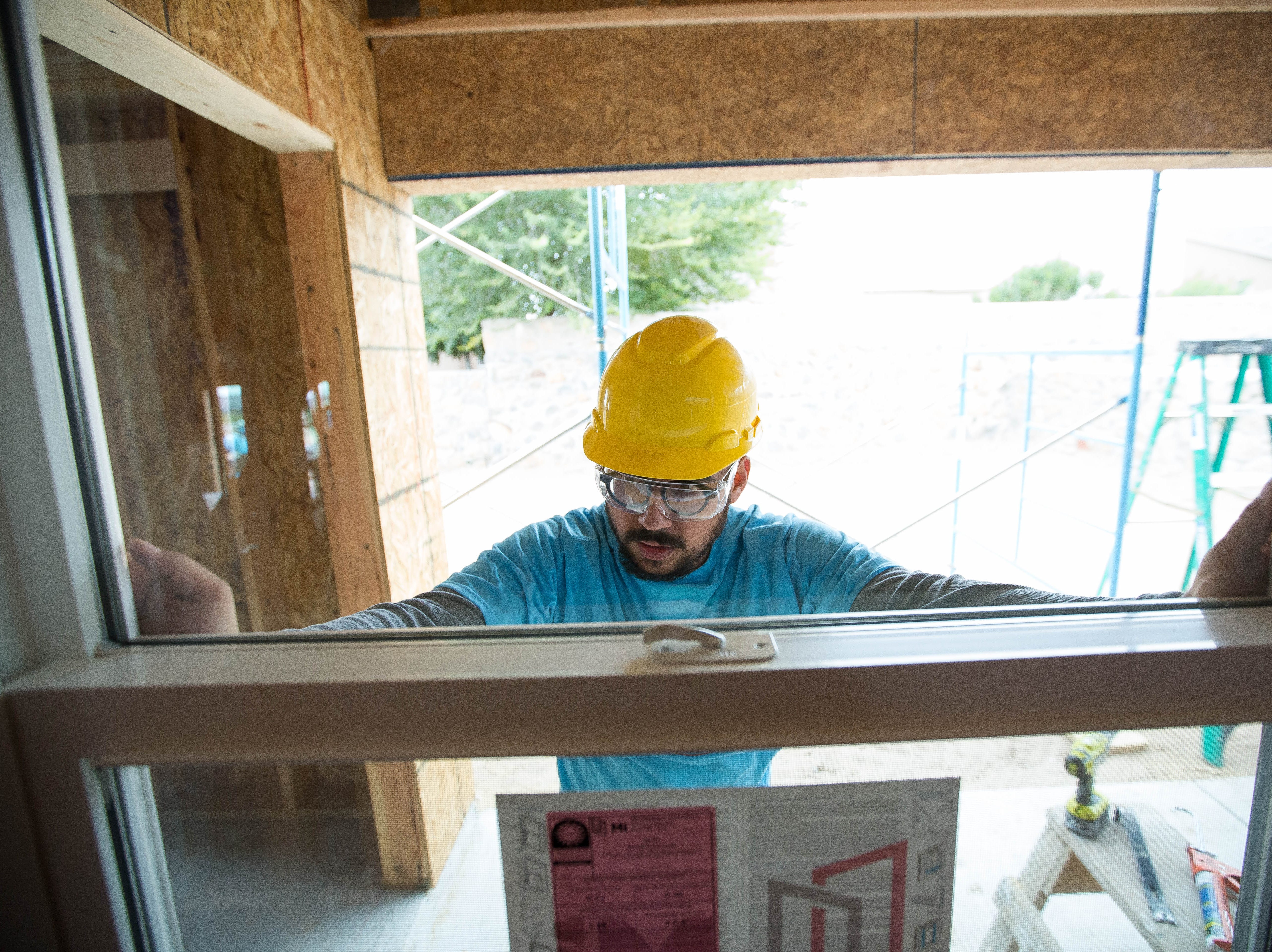 Omar Uribe, the drummer in the Frank Ray band holds up a window as he along with other Habitat for Humanity volunteers work to build homes on Aurora Star Court, Wednesday October 17, 2018.