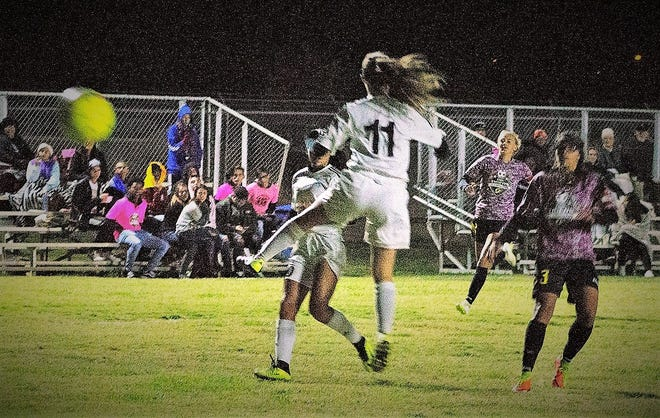 Alamogordo Lady Tiger Shawna Williams (13, left) watches as Oñate Lady Knight Kaitlynn Sprau's (11) blocking attempt of her kick fails to interrupt Williams scoring her third goal.