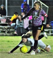 Alamogordo Lady Tiger Sheyenne Drake makes her way past a falling Oñate Lady Knight to score her second goal towards the Lady Tigers 7-3 victory.