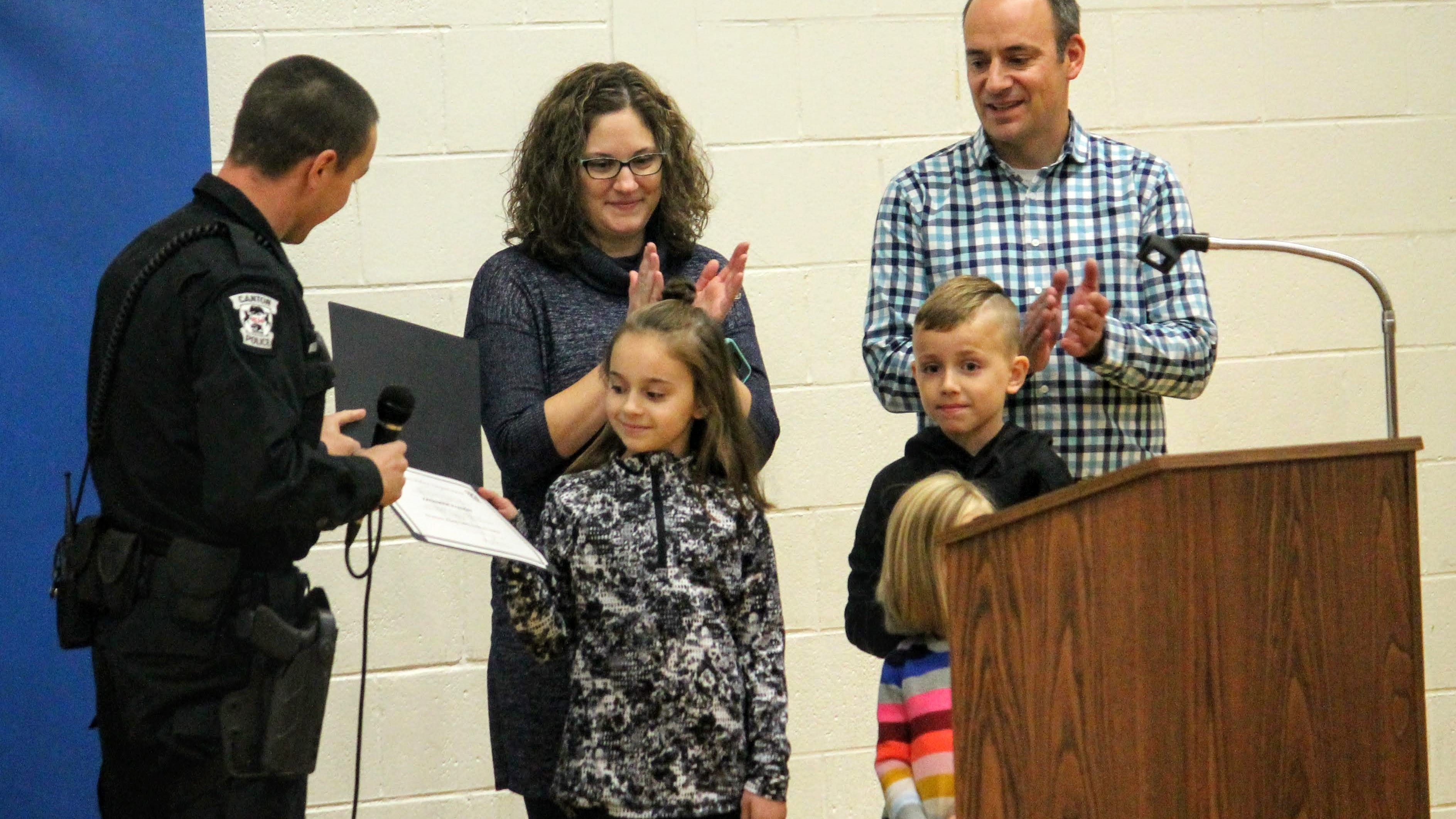 Ten-year-old Kate Evanoff, a fifth grader at Johnson Upper Elementary School in Westland, was recently honored during an assembly at her school for her quick-thinking in getting emergency help for her mother while driving in Canton. Presenting the award is Canton police officer Brian Zinser, who responded to the call. Standing behind Evanoff is her parents and siblings.
