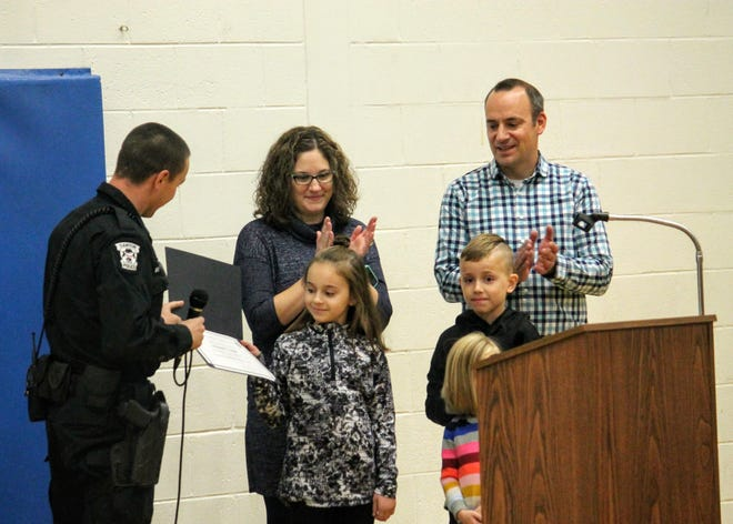 Ten-year-old Kate Evanoff, a fifth-grader at Johnson Upper Elementary School in Westland, was recently honored during an assembly at her school for her quick thinking in getting emergency help for her mother while driving in Canton. Presenting the award is Canton police Officer Brian Zinser, who responded to the call. Standing behind Evanoff are her parents and siblings.