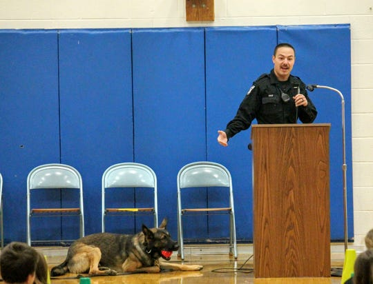 Canton police Officer Brian Zinser speaks at an assembly at Johnson Upper Elementary School in Westland during an assembly Oct. 16. His K-9 partner, Hank, plays with a ball on the gym floor beside him.