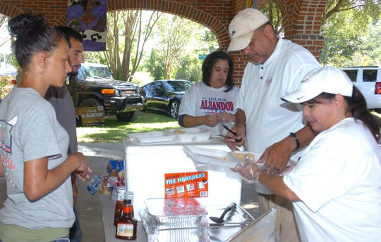Alderman Julius Alsandor distributes free dinners during a campaign rally held recently at the Opelousas Farmers Market.