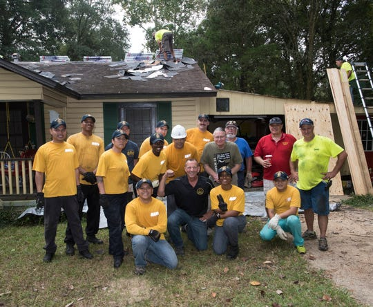 Volunteers from the U.S.S. Tripoli ( LHA-7)  and Diamond Contractors work together on a roofing project for the non-profit organization,  Guns to Hammers, in Pensacola on Wednesday, Oct. 17, 2018.
