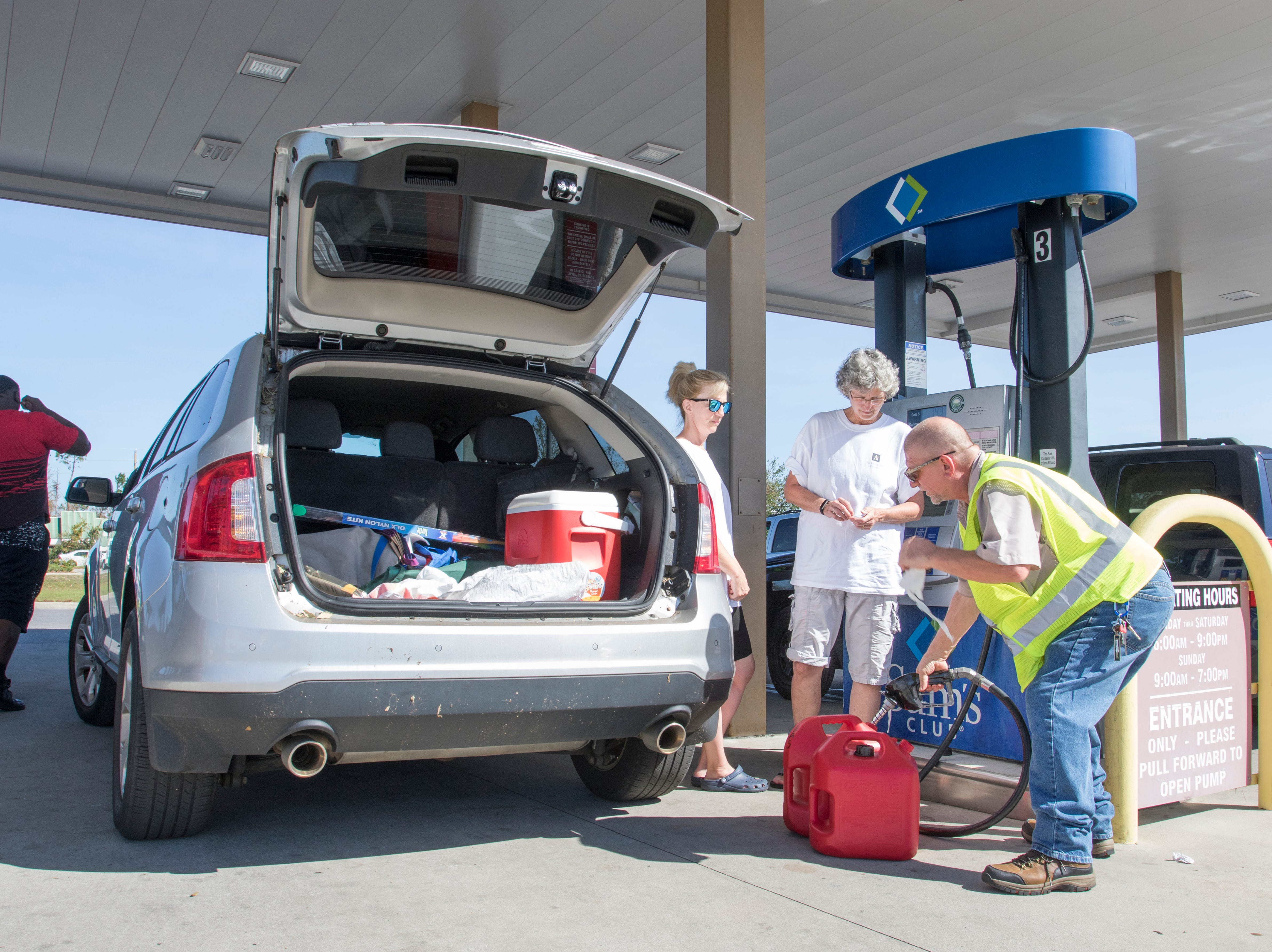 Bob Orlick, of Port Charlotte, Florida, helps fill gas containers for Cathy Meunier, left, and Betsy Straley at the Sam's Club on West 23rd Street in Panama City, Florida on Wednesday, October 17, 2018.  Drivers are thrilled that their wait for gas has gone from up to 4 hours earlier in the week down to 30 to 45 minutes today.