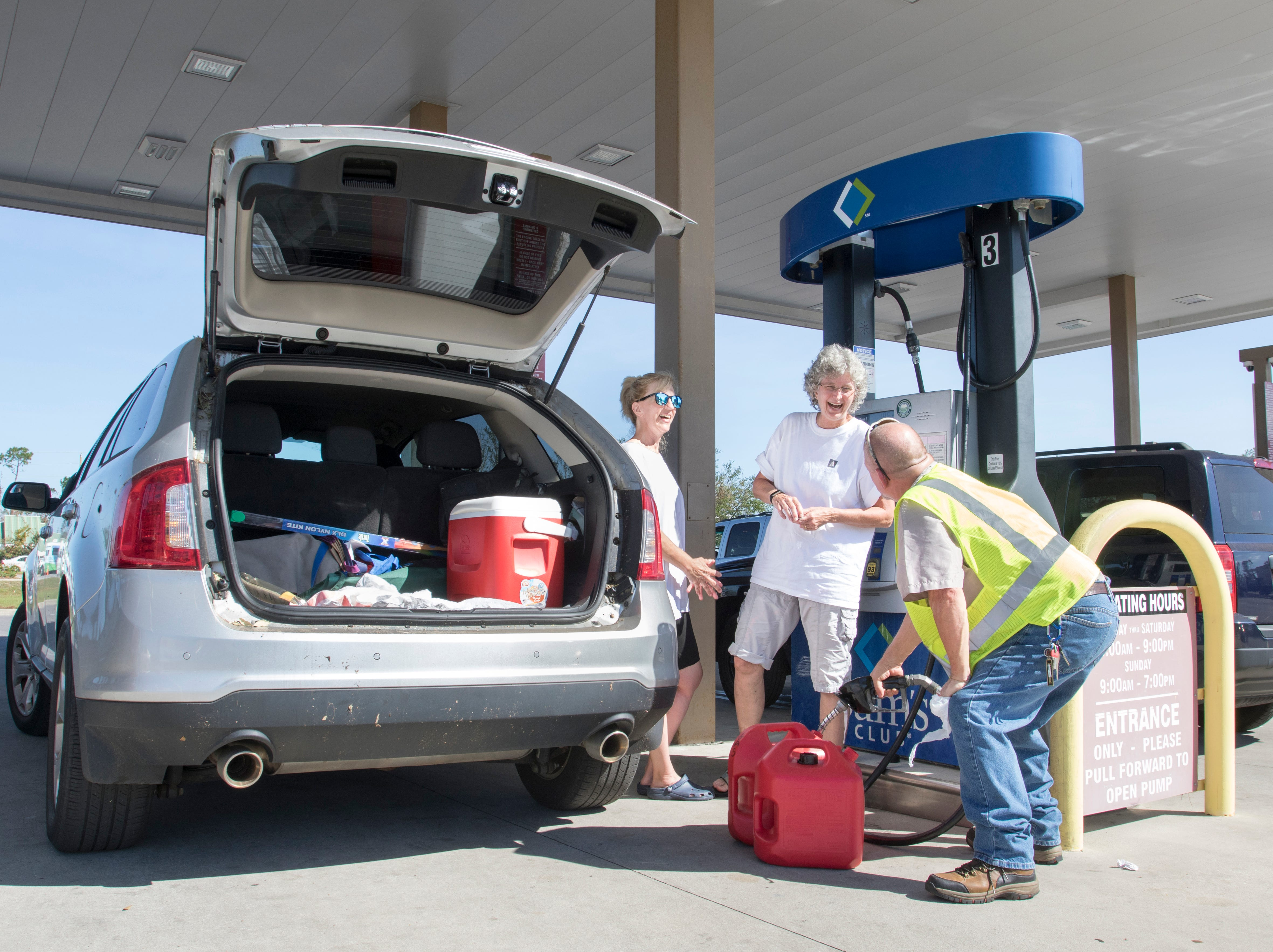 Cathy Meunier, left, and Betsy Straley have a laugh with Bob Orlick, of Port Charlotte, Florida, as he helps fill their gas containers at the Sam's Club on West 23rd Street in Panama City, Florida on Wednesday, October 17, 2018.  Drivers are thrilled that their wait for gas has gone from up to 4 hours earlier in the week down to 30 to 45 minutes today.