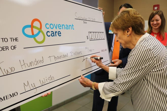 Suzanne Kahn signs a check for $200,000 to Covenant Care on Sept. 27, 2018.