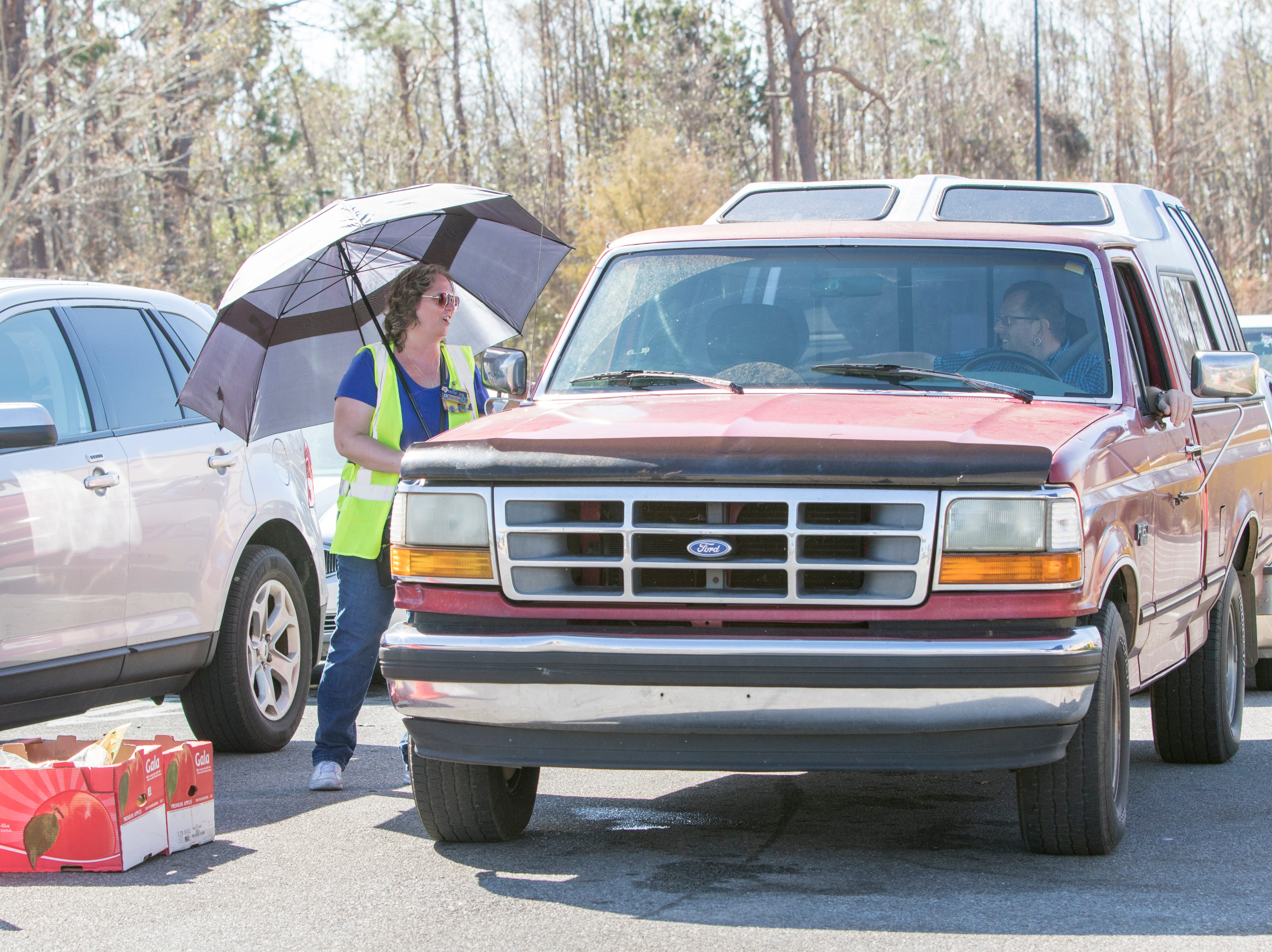 Faith Hawkins, of Kissimmee, Florida, chats with drivers and she controls the flow of vehicles waiting for gas at the Sam's Club on West 23rd Street in Panama City, Florida on Wednesday, October 17, 2018.  Drivers are thrilled that their wait for gas has gone from up to 4 hours earlier in the week down to 30 to 45 minutes today.