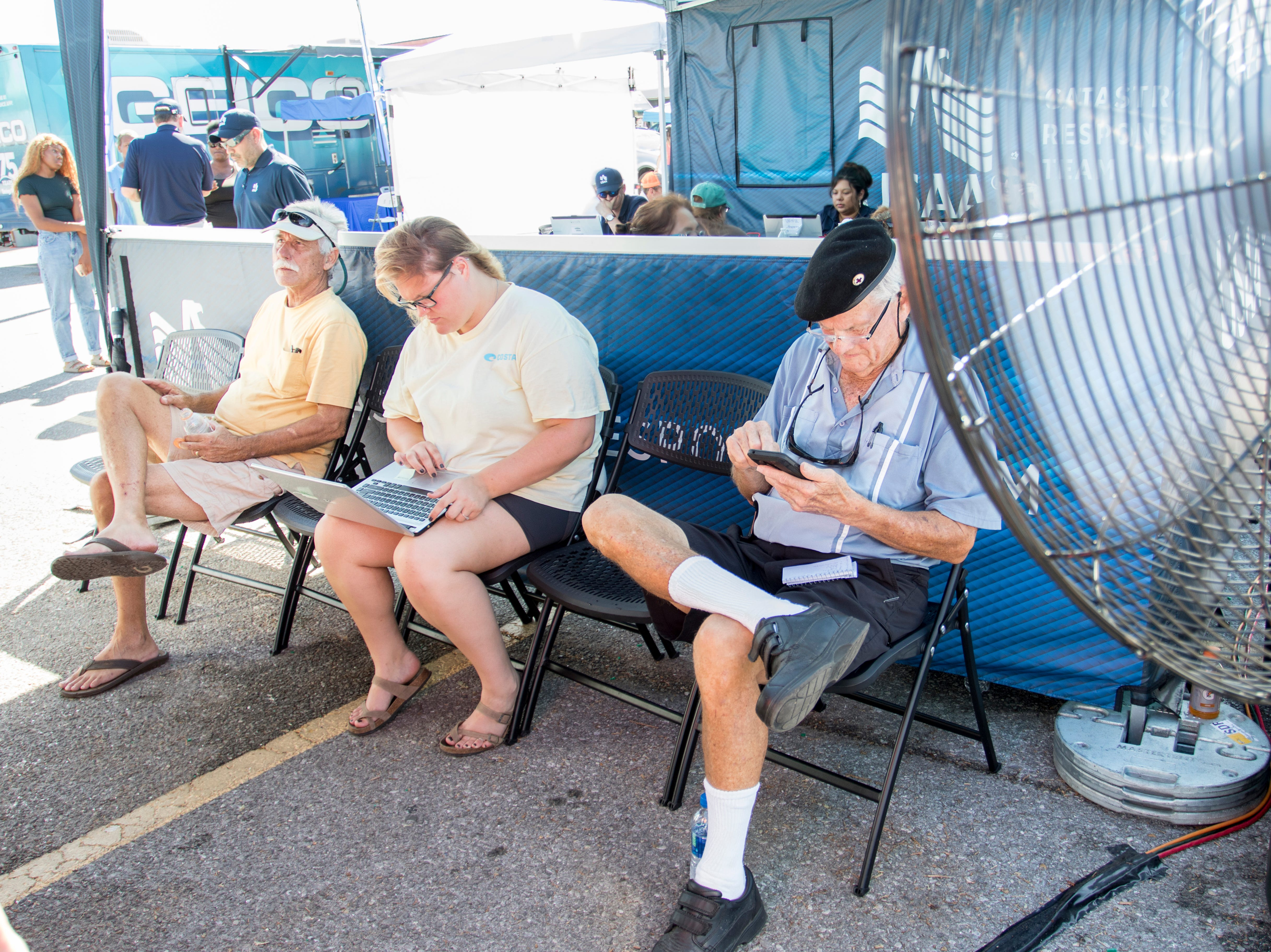 Sitting in the breeze of a fan, Courtney Galbreath takes advantage of wifi access while Jack Ball, left, and Jay Currier wait to file claims with USAA at the insurance village that as been set up on West 23rd Street to service clients affected by Hurricane Michael in Panama City, Florida on Wednesday, October 17, 2018.