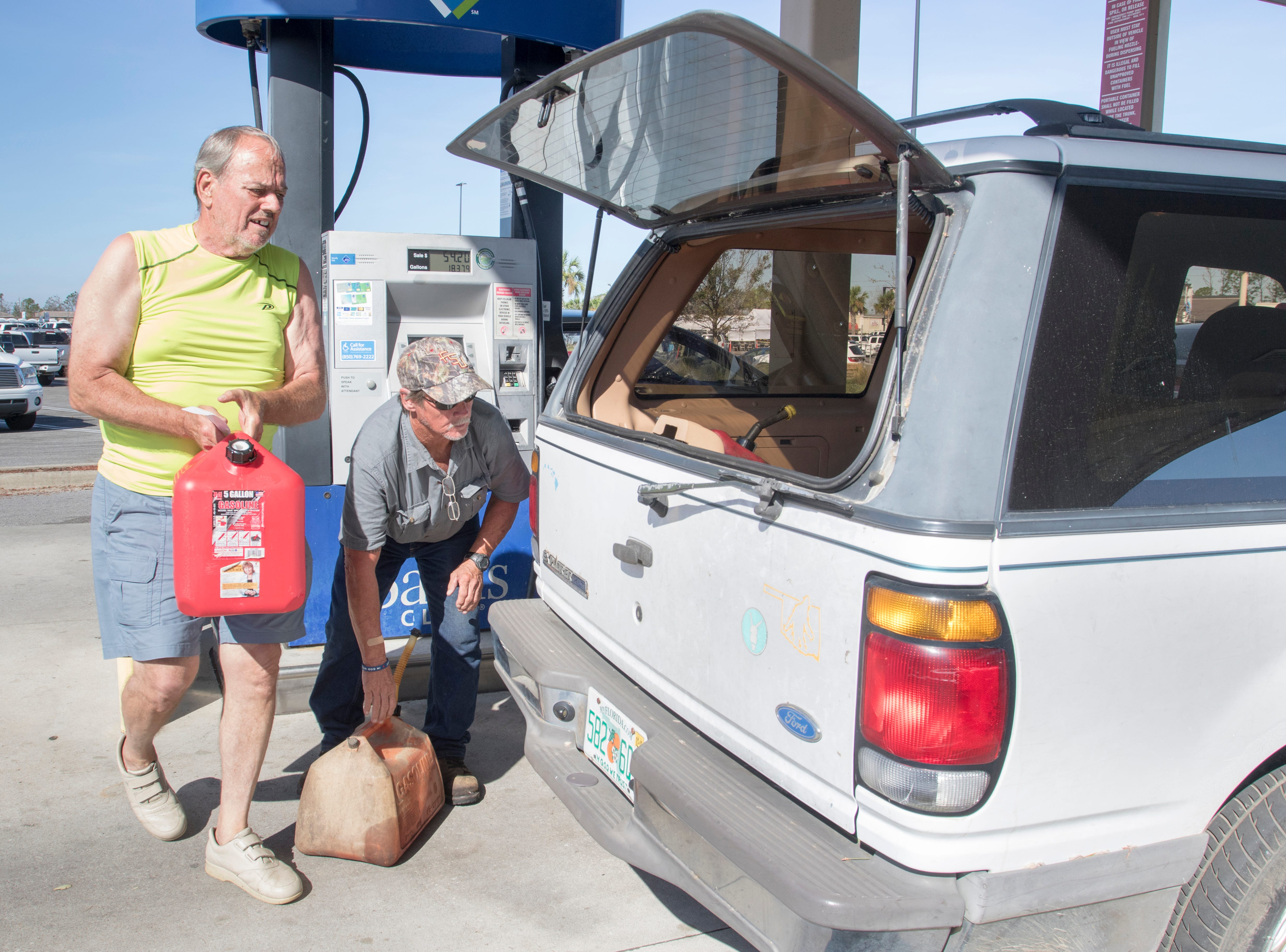 Larry Holland, left, and Thomas Johnson load filled gas cans into their vehicle at the Sam's Club on West 23rd Street after Hurricane Michael in Panama City, Florida on Wednesday, October 17, 2018.    Drivers are thrilled that their wait for gas has gone from up to 4 hours earlier in the week down to 30 to 45 minutes today.