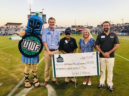 Howard Reddy, Hal Marcus, Martha Saunders and Jaromy Kuhl pose with a check at Wahoos Field on Sept. 15, 2018.