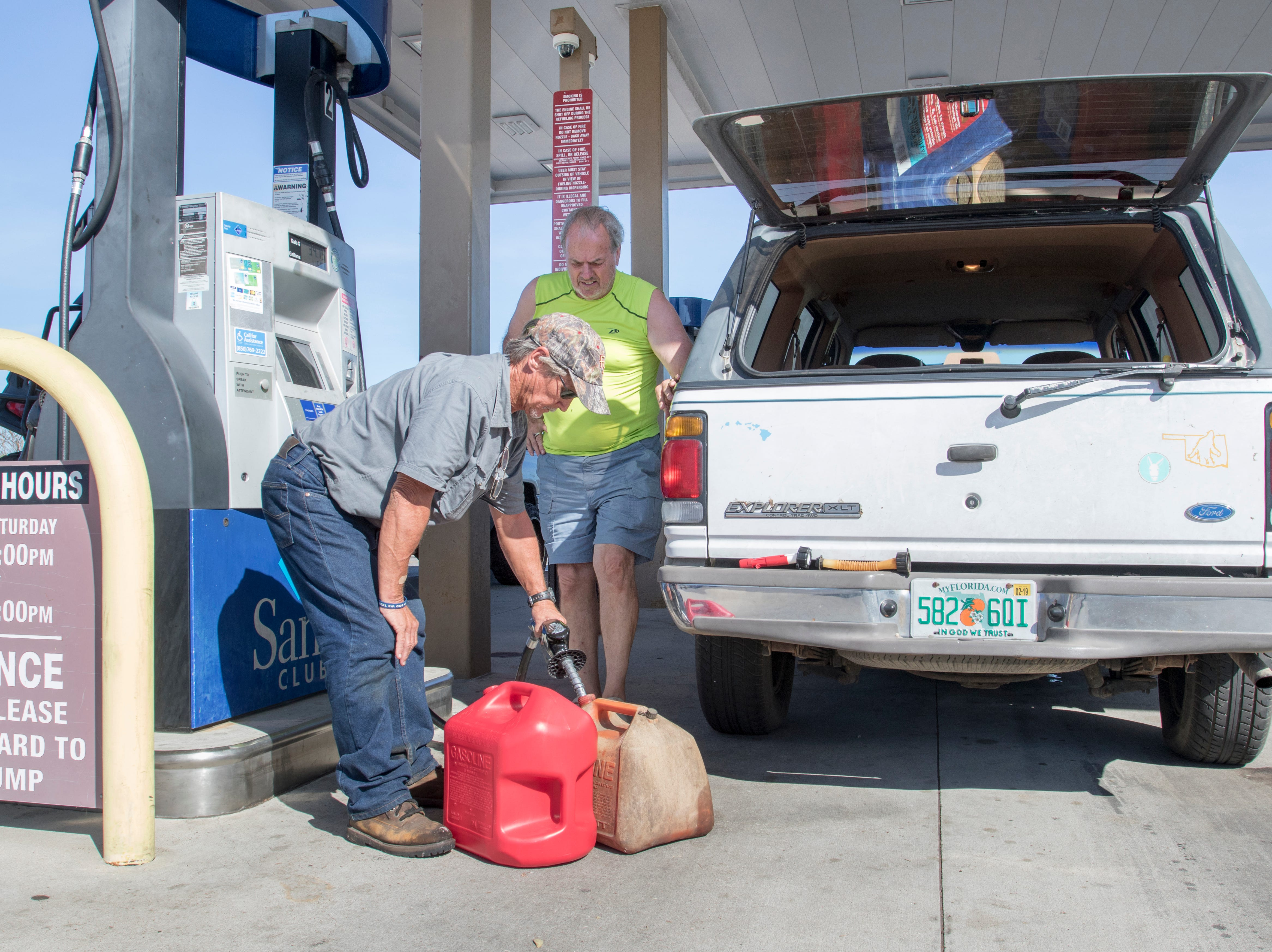 Thomas Johnson, left, and Larry Holland fill up gas cans at the Sam's Club on West 23rd Street after Hurricane Michael in Panama City, Florida on Wednesday, October 17, 2018.    Drivers are thrilled that their wait for gas has gone from up to 4 hours earlier in the week down to 30 to 45 minutes today.