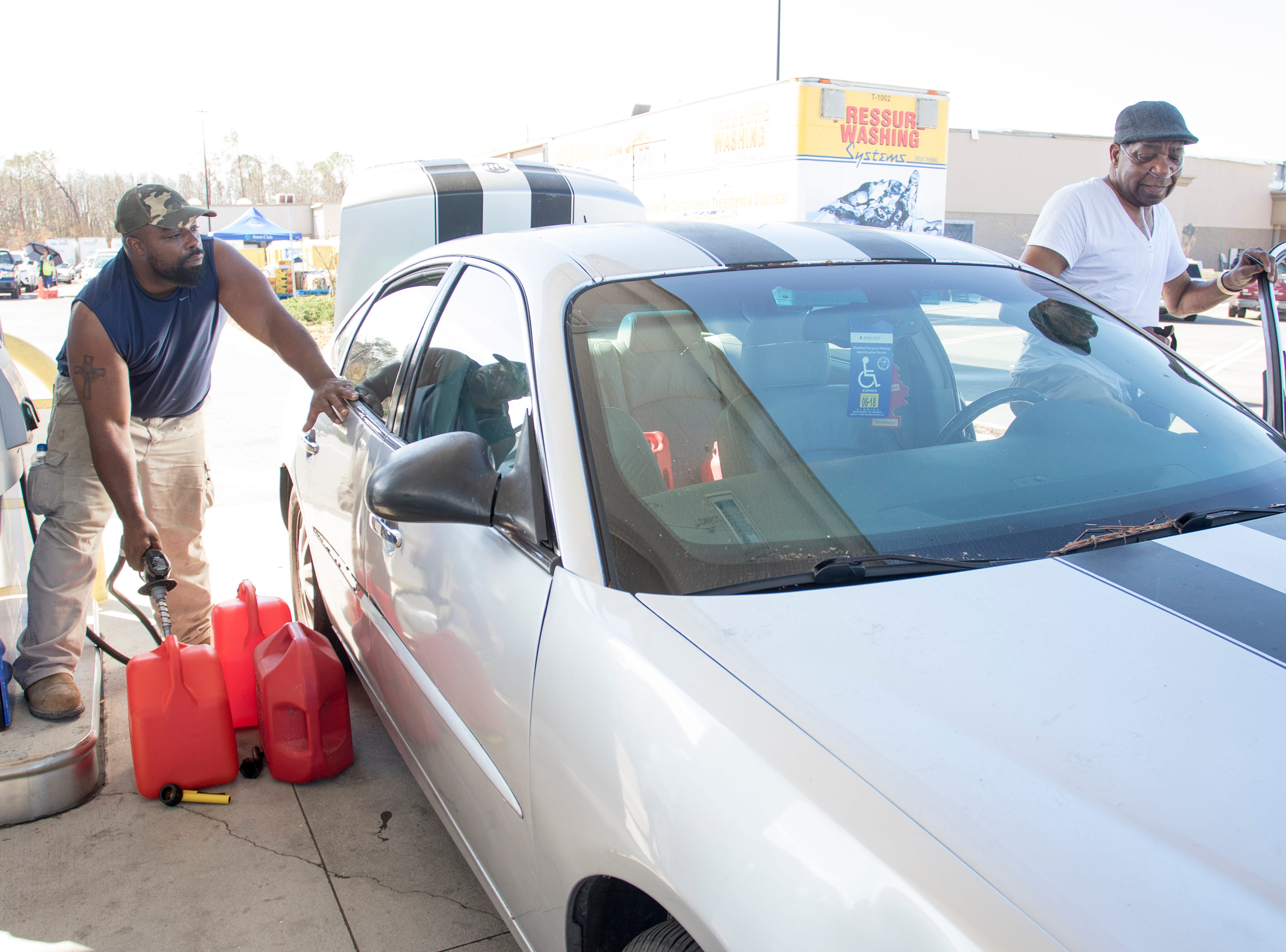 Michael Ross, left, fills gas containers as he father Jimmy Curry, 78, gets back into the car at the Sam's Club on West 23rd Street in Panama City, Florida on Wednesday, October 17, 2018.  Drivers are thrilled that their wait for gas has gone from up to 4 hours earlier in the week down to 30 to 45 minutes today.